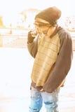 De jonge openlucht sprekende telefoon van de rastakerel met een warme toegepaste filter Stock Afbeeldingen