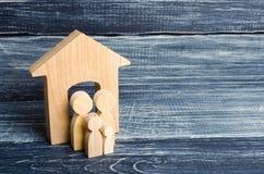 De jonge ouders en een kind bevinden zich dichtbij hun huis Concept die onroerende goederen, en een huis kopen verkopen Betaalbar stock foto's