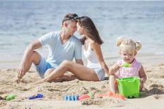 De jonge ouders omhelzen elkaar als hun kleine dochter playin royalty-vrije stock afbeeldingen