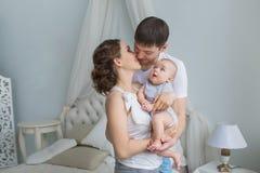 De jonge ouderskus elkaar en hun kleine baby bekijkt hun stock fotografie