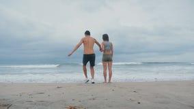 De jonge paarholding overhandigt tribunes voor oceaan bij strand de mens loopt comically vanaf de golf stock video