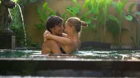 De jonge de paarvrouw en man hebben pret in hun privé zwembad Wittebroodswekenconcept