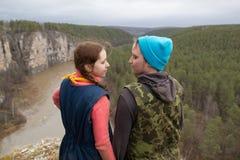 De jonge paarwandelaars die zich op de rand van een klip bevinden en holdind overhandigt de bergrivier Royalty-vrije Stock Afbeeldingen