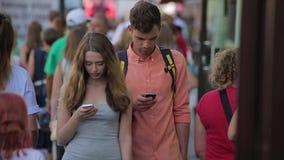 De jonge paarwandeling langs de bezige stadsstraat en bekijkt hun mobiles in slo-mo stock videobeelden