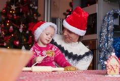 De jonge papa en weinig dochter in Kerstmanhoed bakken Stock Foto's
