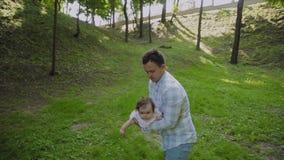 De jonge papa houdt de baby in zijn wapens stock footage