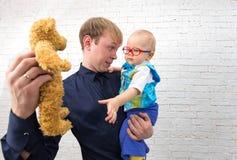 De jonge papa toont teddybeer aan zijn één éénjarigezoon op baksteenrug Royalty-vrije Stock Afbeeldingen