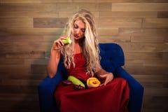 De jonge peinzende vegetarische vrouw zit op leunstoel op achtergrond van houten muur stock foto's