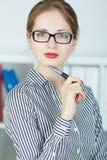 De jonge pen van de bedrijfsvrouwenholding dichtbij het gezicht die portret in camera kijken Royalty-vrije Stock Fotografie