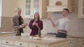 De jonge de pizzamaker en vrienden jongleren met ballen van deeg in de keuken Pizza het koken art. stock videobeelden