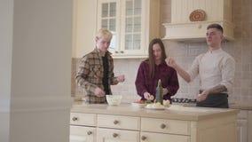 De jonge pizzamaker jongleert met ballen van deeg in de keuken, aantonend zijn vaardigheden aan zijn vrienden Glimlachende Man en stock footage
