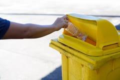 De jonge plastic fles van de jongenshand trow in een gele bak royalty-vrije stock afbeeldingen