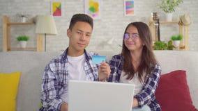 De jonge positieve sian paarzitting bij laptop gebruikt een creditcard en onderzoekt de camera stock videobeelden