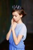 De jonge prinses met een kroon op zijn hoofd in een blauwe stan kleding Stock Afbeeldingen