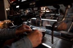 De jonge professionele baristamens bereidt heerlijke hete koffie in een moderne koffiemachine voor royalty-vrije stock foto's
