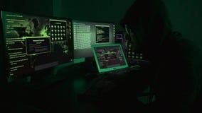 De jonge programmeur van de hakkermens in zijn zwart digitaal bedrijfswerk stock videobeelden