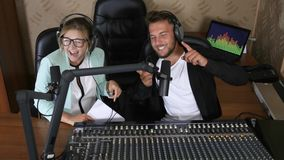 De jonge radiogastheerkerel en de vrouw in oortelefoons spreken in microfoon dichtbij correcte console bij radiouitzending stock footage