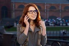 De jonge redheaded vrouw met sproeten loopt in de avond stad en het spreken op de telefoon royalty-vrije stock afbeelding