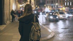 De jonge reizende vrouw die met rugzak de verkeersweg, toerist het kijken kruisen rond en vindt de manier in de avond Stock Afbeelding