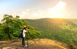 De jonge reizende vrouw met rugzakhoed en de camera op driepoot bevinden zich op de bovenkant van de bergklip lettend op mooie me stock foto's