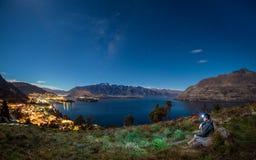 De jonge reiziger geniet nacht van scène van queenstown, Nieuw Zeeland stock foto