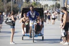 De jonge riksja geeft een lift aan vrolijke toeristen langs het strand in Barcelona, Spanje Stock Fotografie