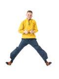 De jonge roodharige jongen in een gele jasje springende jongen met handen klemde in een vuist dicht en hief omhoog zijn duim op Stock Fotografie