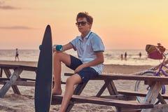 De jonge schaatserjongen in zonnebril kleedde zich in t-shirt en borrels zittend op een bank tegen de achtergrond van de zeekust royalty-vrije stock fotografie