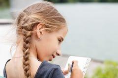 De jonge schets van de meisjestekening in notitieboekje dichtbij vijver royalty-vrije stock foto's