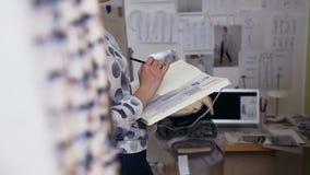 De jonge schets van de de vrouwentekening van de manierontwerper van modieuze kleren stock footage
