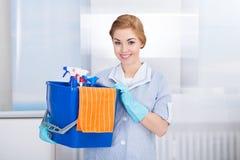 De jonge schoonmakende levering van de meisjeholding royalty-vrije stock afbeeldingen
