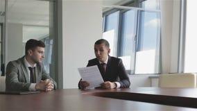 De jonge schrijver en de directeur van de uitgeverij zijn in het bureau stock videobeelden