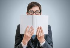 De jonge schuwe mens leest en verbergt zijn gezicht achter boek Royalty-vrije Stock Fotografie