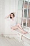 De jonge sensuele vrouw met verse dagelijks maakt omhooggaand en romantisch golvend kapsel, zittend bij de vensterbank in man vri Royalty-vrije Stock Foto