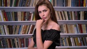 De jonge seroiusvrouw let op bij camera, het denken concept, boekenrek op achtergrond stock video