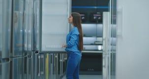 De jonge sexy donkerbruine vrouw in overhemd om de deur van de ijskast in de toestellen te openen slaat en is met andere op verge stock videobeelden