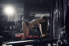 De jonge sexy training van het geschiktheidsmeisje met domoren in de gymnastiek, vrouw met perfect spierlichaam Royalty-vrije Stock Foto's