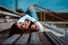 De jonge sexy vrouw ligt op een houten bank Zij neemt onderbreking na training in gymnastiek openlucht royalty-vrije stock fotografie