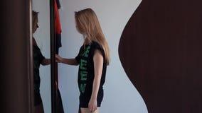 De jonge sexy vrouw opent de deur van de spiegellade, kiezend kleren in ochtend stock videobeelden