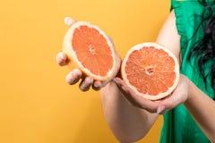 De jonge sinaasappelen van de vrouwenholding stock foto