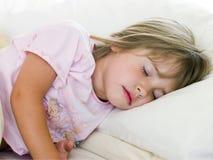 De jonge Slaap van het Meisje in Haar Bed Stock Afbeelding