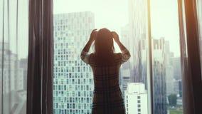 De jonge slanke die vrouw aan het venster in werking wordt gesteld onthult gordijnen en bewondert zonsondergangmening thuis van h stock video