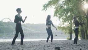 De jonge slanke man en twee mooie vrouwen presteren gelijktijdig tonen met vlam terwijl status voor weg en hout stock footage