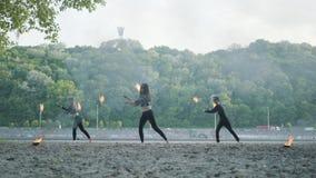 De jonge slanke man en twee mooie vrouwen presteren gelijktijdig tonen met vlam terwijl status voor weg en hout stock video