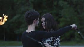 De jonge slanke man in zwarte kleren en de aantrekkelijke vrouw presteren tonen in openlucht met vlam Het bekwame fireshowkunsten stock videobeelden
