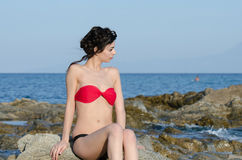 De jonge slanke mooie de bikinizitting van de dameslijtage op overzeese rotsen staart de oceaan Stock Fotografie