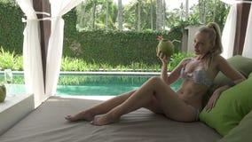 De jonge slanke vrouw heeft een rust in de tropische toevlucht onder palmen stock footage