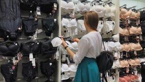 De jonge slanke vrouw kiest een bustehouder in een ondergoedopslag stock video