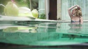 De jonge slanke vrouw met lang haar heeft een rust in de pool en drinkt cocktail van kokosnoot in de tropische toevlucht stock videobeelden