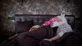 De jonge slaperige vrouw in pyjama wekt de ongebruikelijke mens stock videobeelden